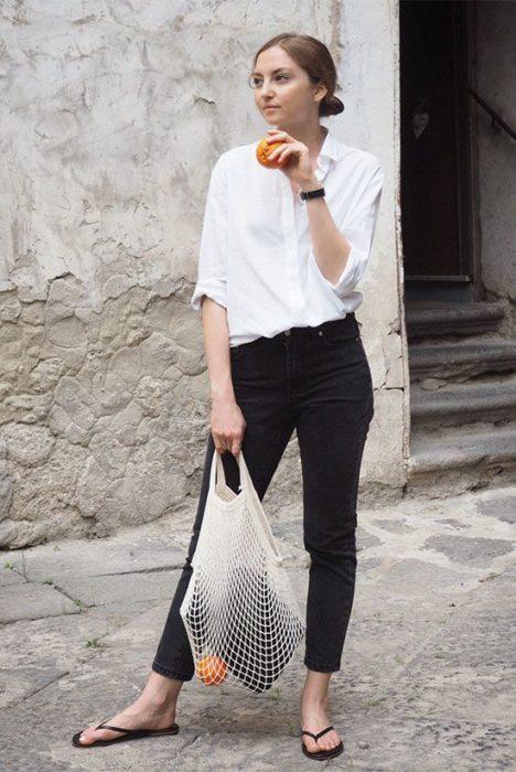 Chica con pantalón negro, blusa blanca y flip flops