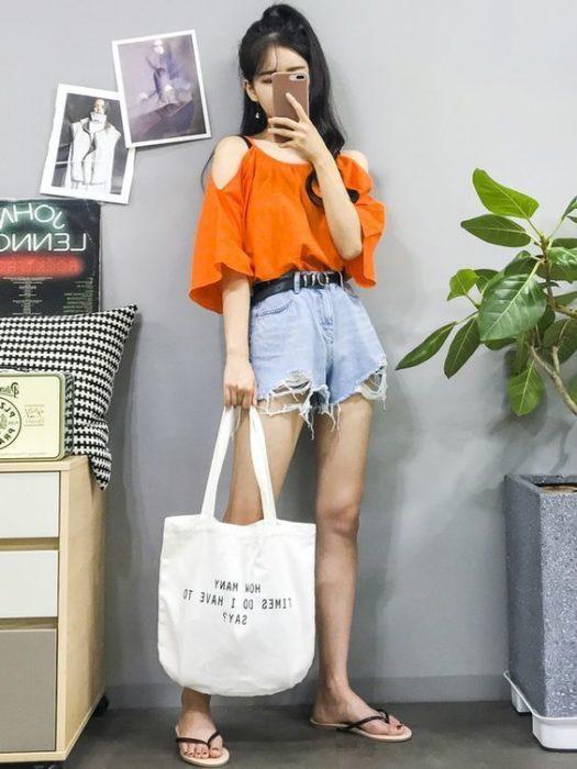 Chica asiática con blusa holgada naanja, shorts de mezclilla y flip flops