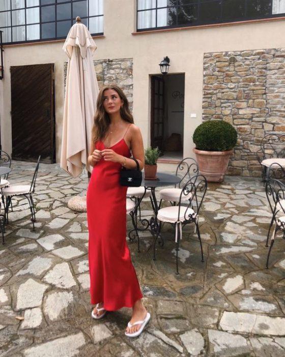 Chica delgada con vestido rojo largo y flip flops blancas