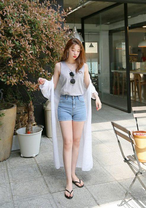 Chica caminando por la calle con short de mezclilla y blusa gris con flip flips negras