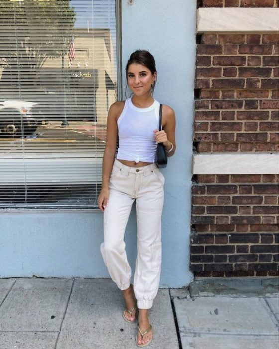 Chica posando en una pared usando blusa blanca y pantalón beige y flip flops blancas