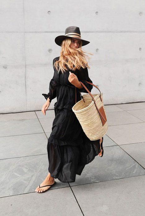 Chica rubia con vestido largo negro camina por la calle con flip flops