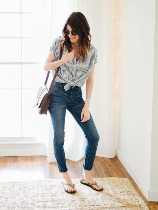 Chica posando con jenas oscuros, blusa gris y flip flops negros