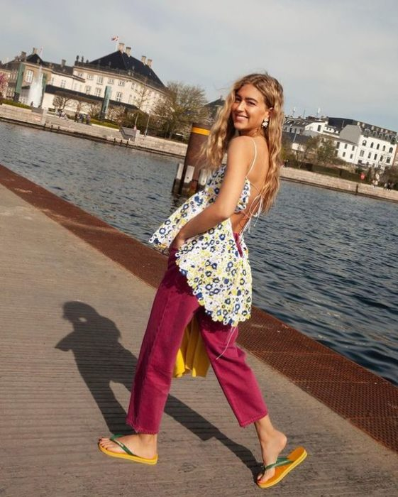 Chica rubia caminar por un lago con pantalón rosa y flip flops