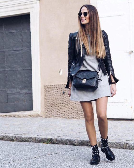 Chica con vestido gris, chaqueta de cuero negra ya botines con estoperoles