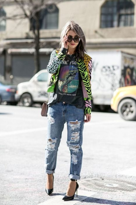 Chica con jeans rotos, blusa negra y saco de animal print color verde
