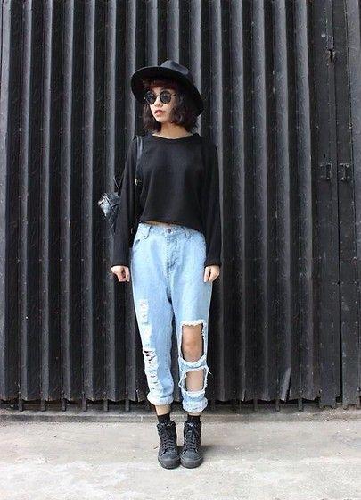 Chica con pantalones rotos, suéter negro y sombrero negro