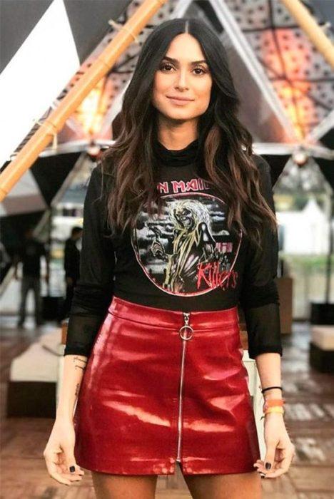 Chica morena de cabello castaño con blusa negra y falda de cuero roja