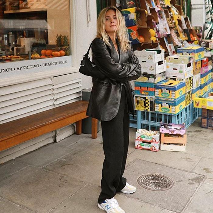 chica rubia con cabello largo usando una chaqueta de cuero larga, pantalones de vestir negros y tenis deportivos, bolso de mano negro