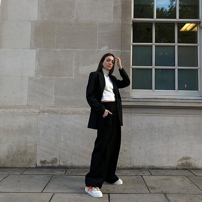 chica de cabello castaño con top blanco de cuello alto, blazer negro y pantalones negros de vestir, tenis deportivos