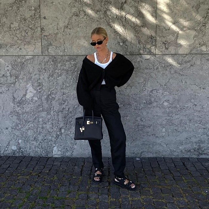 chica rubia con lentes de sol, top blanco de tirantes, sueter negro y pantalon de vestir negro