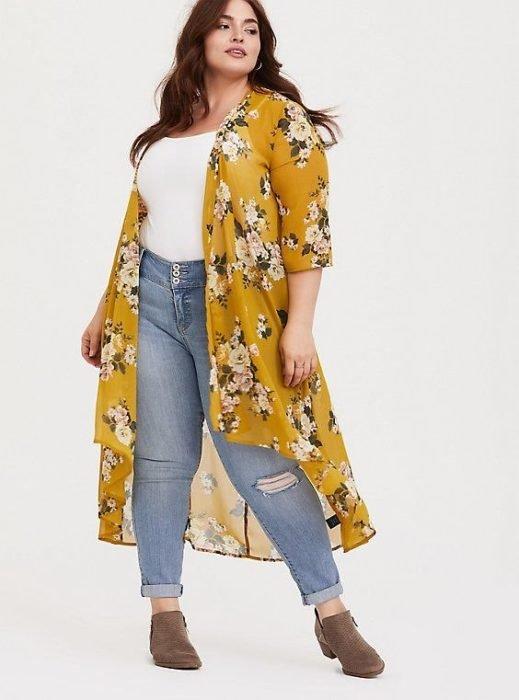 Chica usando outfit veraniego de jeans denim, top blanco, ensamble amarillo con estampado de flores y botines