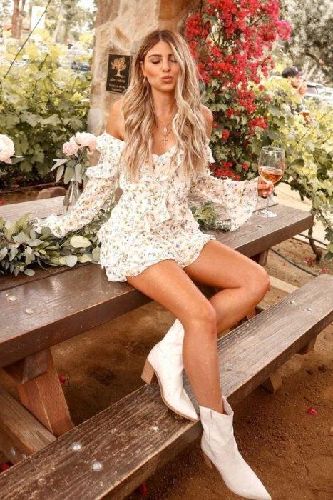 Chica usando outfit veraniego de vestido blanco corto, de manga larga y botines blancos