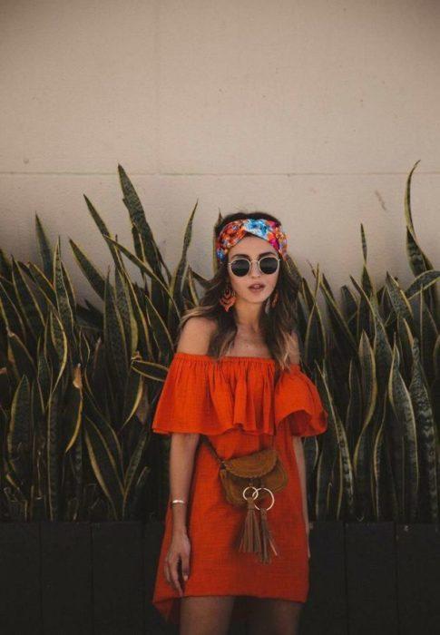 Chica usando outfit veraniego de vestido naranja off the shoulder, arriba de la rodilla, con lentes oscuros banda en el cabello y bolso cruzado
