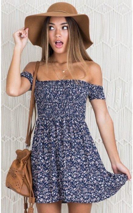 Chica usando outfit veraniego de vestido azul con vuelo y off the shoulder, usando sombrero y bolsa color camel
