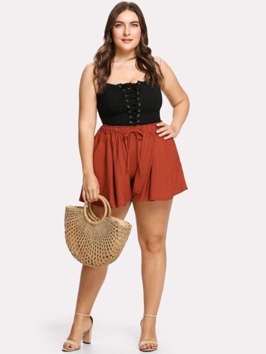Chica usando outfit veraniego de shorts casuales color ladrillo top negro, junto con bolsa de paja y tacones