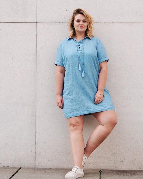Chica usando outfit veraniego de vestido arriba de la rodilla, estilo denim, y tenis blancos