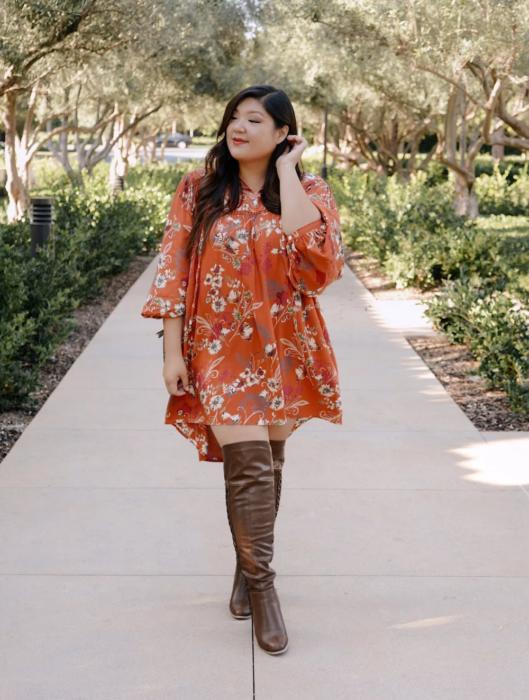 Chica usando outfit veraniego de vestido naranjana con estampado, manga 3/4 y botas altas cafés