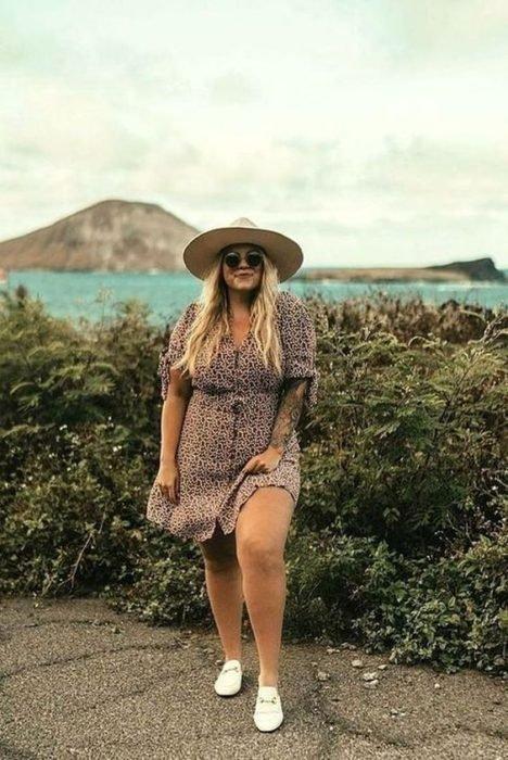 Chica usando outfit veraniego de vestido color café con botones, tenis blancos, lentes oscuros y sombrero de paja