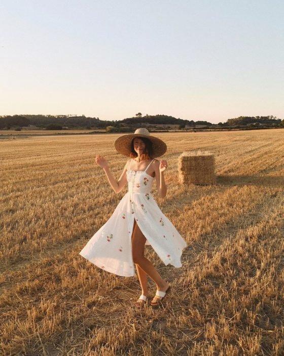 Chica usando outfit veraniego de vestido con vuelo, color blanco y estampado, y abertura de un lado y sombrero de paja
