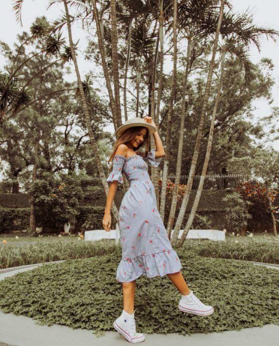 Chica usando outfit veraniego de vestido midi, off the shoulder, tenis blancos, y sombrero de paja