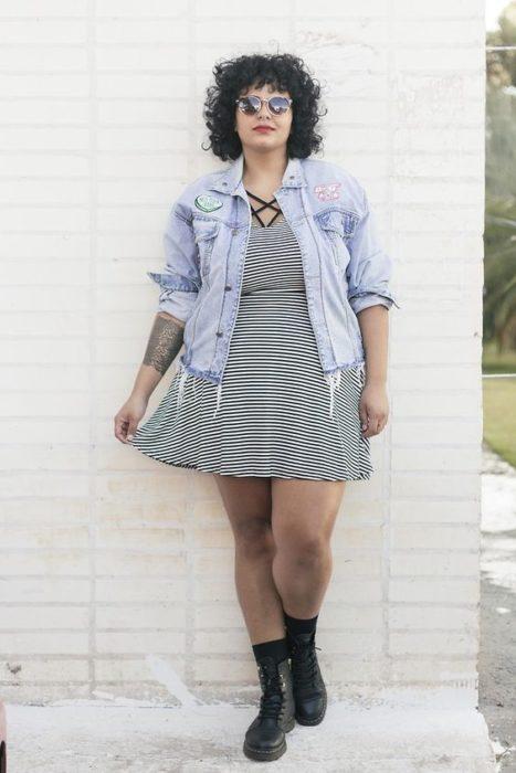 Chica plus size con vestido de rayas blanco con negro y chamarra de mezclilla