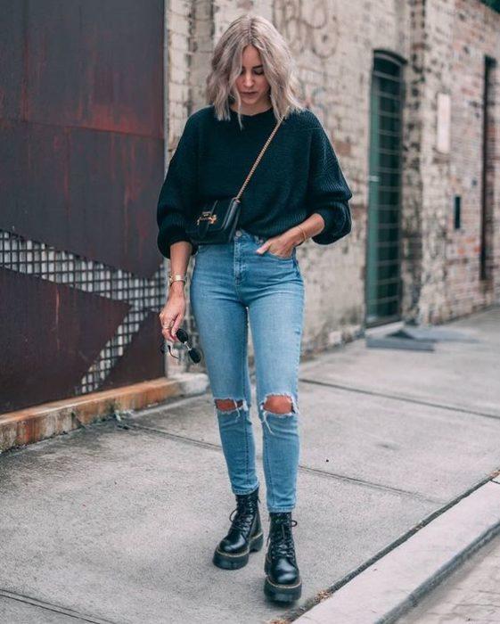 Chica rubia de melena corta con supeter azul marino oversised y jeans rotos de las rodillas con botas dr. martens negras