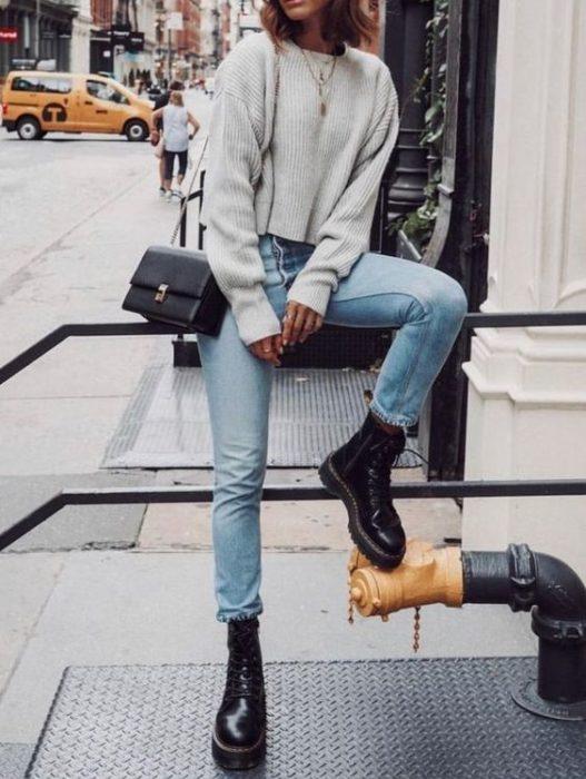 Chica sentada en barandal con suéter gris oversized, jeans azulesm bolso negro cuadrado en el hombro y boas dr. martens negras