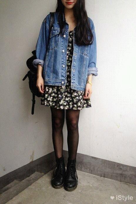 Chica morena de cabello lago y oscuro con vestido corto floreado y chaqueta de mezclilla usando botas dr. martens