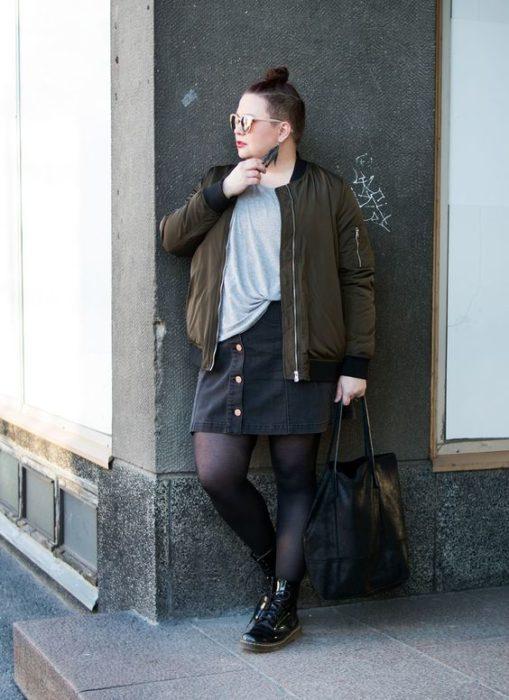 Chica plus size recargada en la pared con chaqueta verde militar, blusa gris, falda negra, medias negras y botas dr. martnes