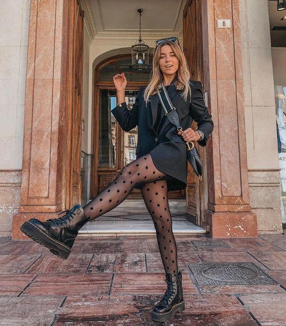 Chica rubia dando una patada al aire con chaqueta y vestido negros y medias negras transparentes con bolitas y botas negras dr. martens