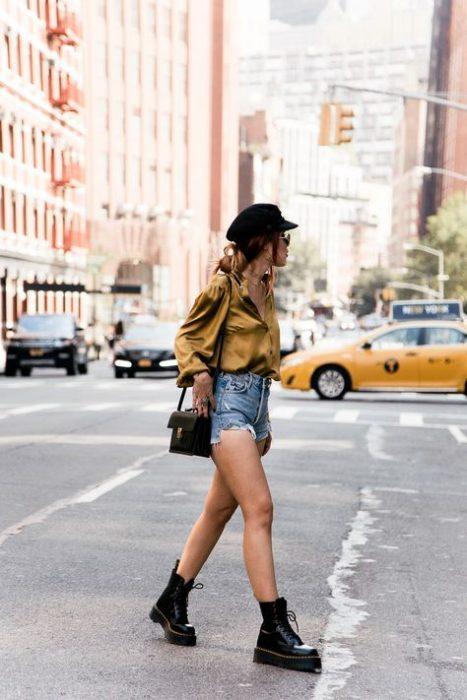 Chica rubia de cabello largo suelto con gorro negro y blusa amarilla de manga larga con short de mezclilla y botas dr. martens negras