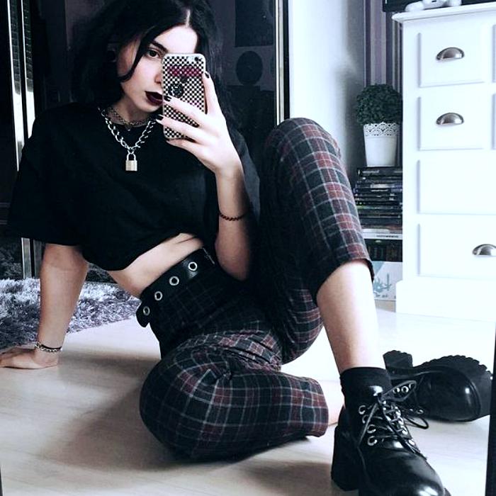 chica de cabello negro usando camiseta crop-top negra, cinturón de estoperoles, pantalón de cuadros negros y guindas con botas de cuero de plataforma