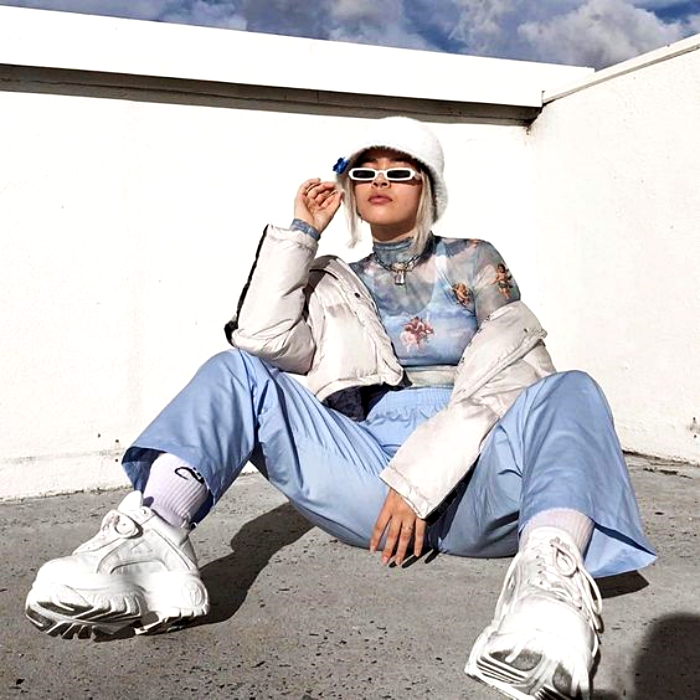 chica con cabello platinado usando un bucket-hat blanco, top con estampado de nubles, chamarra blanca, pantalones azul celeste baggy y tenis deportivos blancos