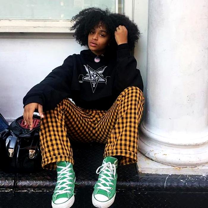 chica morena con cabello chino usando una sudadera negra con estampado y pantalones amarillos con cuadros negros, converse verdes