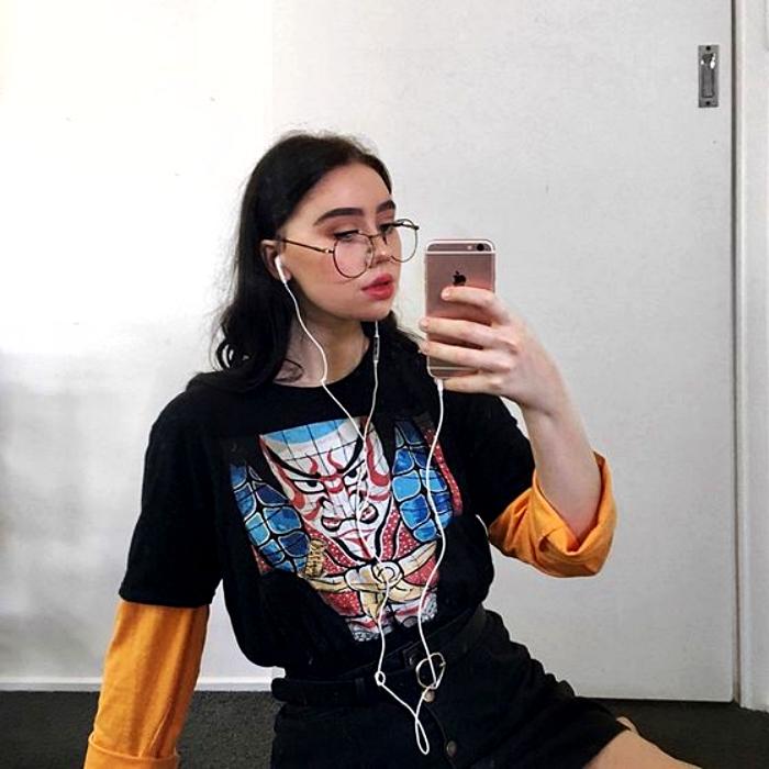 chica de cabello castaño con lentes usando una camiseta negra con estampado, mangas anaranjadas y minifalda negra