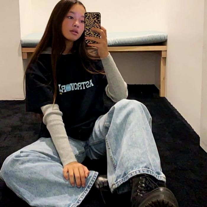 chica de cabello largo castaño usando una camiseta negra de astroworld con mangas grises, pantalón de mezclilla baggy y botas negras de plataforma